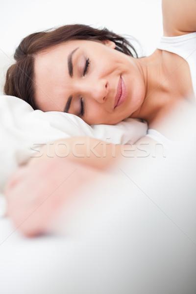 Brunette woman closing her eyes while lying in her bedroom Stock photo © wavebreak_media