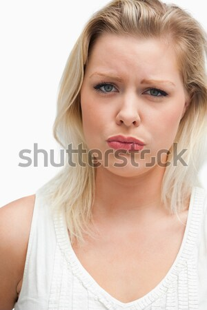 Upset blonde woman seriously looking at the camera against a white background Stock photo © wavebreak_media