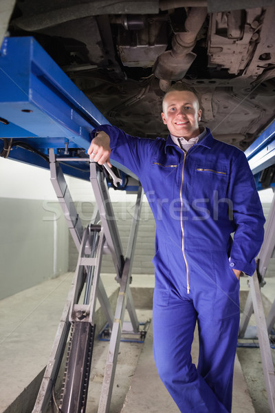 Mechanic leaning on a machine while holding a spanner in a garage Stock photo © wavebreak_media