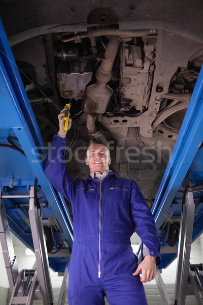 Smiling mechanic repairing a car with an adjustable pliers in a garage Stock photo © wavebreak_media