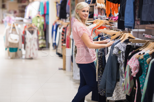 Woman is standing in a shop searching for clothes Stock photo © wavebreak_media