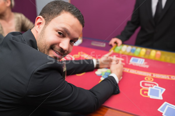 Man looking up from claiming his winnings from poker game in casino Stock photo © wavebreak_media
