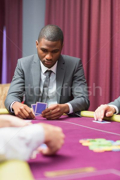 Foto stock: Homem · olhando · cartões · tabela · pôquer · cartão