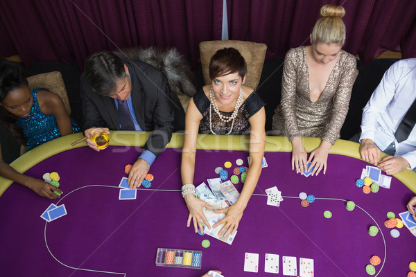 Stock photo: Woman taking the pot at poker game in casino