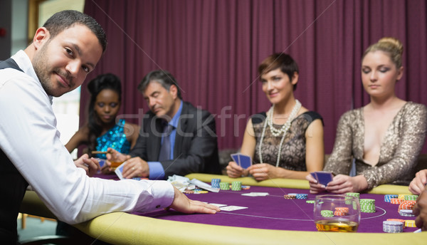 Stock photo: Dealer smiling at poker game in casino