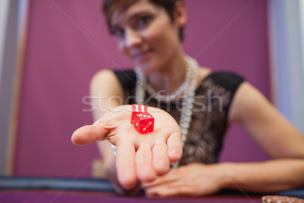 Woman sitting at table in a casino holding dices and smiling Stock photo © wavebreak_media