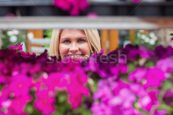 Mulher olhando flor prateleira sorrindo sorridente Foto stock © wavebreak_media