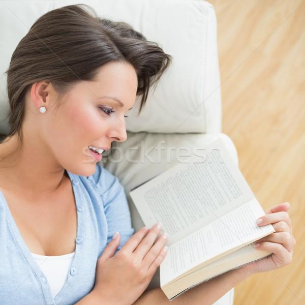 Smiling brunette reading a novel lying on the sofa in the living room Stock photo © wavebreak_media