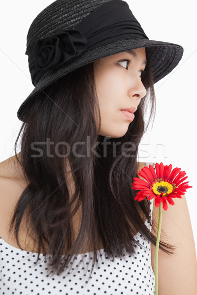 Woman with flower looking away wearing hat and polka dots on white background Stock photo © wavebreak_media