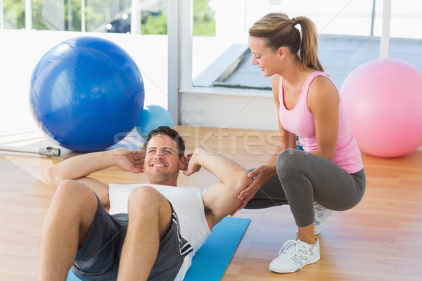 Female trainer looking at young man do abdominal crunches Stock photo © wavebreak_media