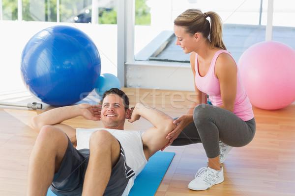 Feminino treinador olhando moço abdominal Foto stock © wavebreak_media