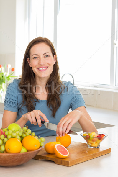 Portrait of a woman cutting fruits in kitchen Stock photo © wavebreak_media