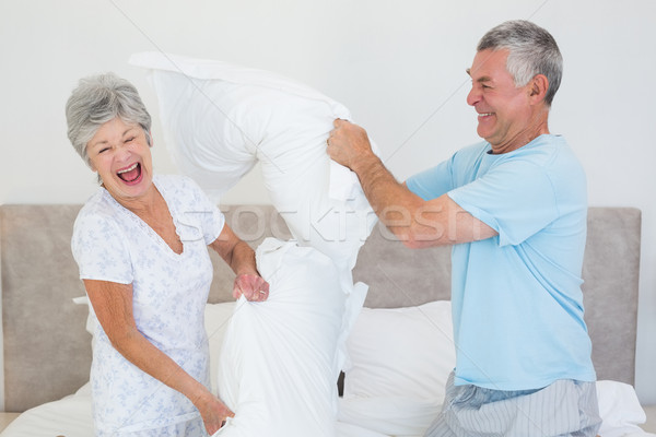 Stock photo: Senior couple having pillow fight in bed