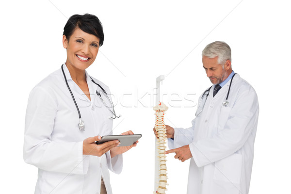 Doctor holding digital table with colleague by skeleton model Stock photo © wavebreak_media