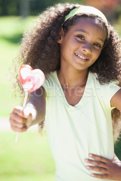 Young girl holding a heart lollipop in the park  Stock photo © wavebreak_media