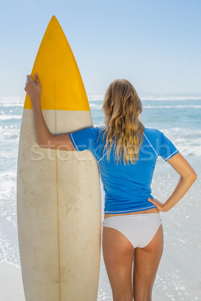 Blonde surfer holding her board on the beach  Stock photo © wavebreak_media