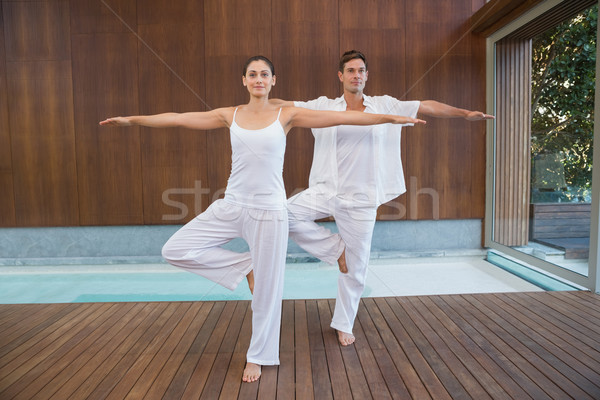 Peaceful couple in white doing yoga together in tree position Stock photo © wavebreak_media