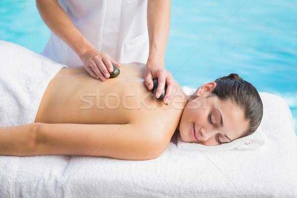 Happy brunette getting a hot stone massage poolside Stock photo © wavebreak_media