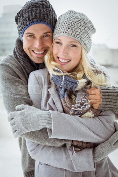 Cute couple in warm clothing smiling at camera Stock photo © wavebreak_media