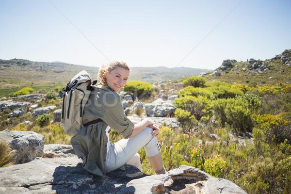 Pretty hiker sitting at the summit smiling at camera Stock photo © wavebreak_media