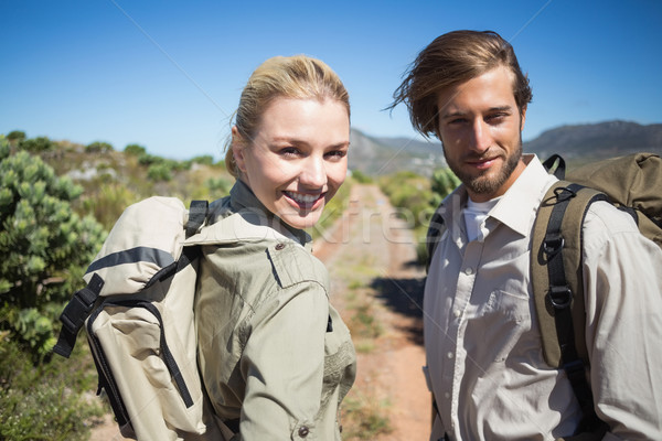 Hiking couple walking on mountain terrain smiling at camera Stock photo © wavebreak_media