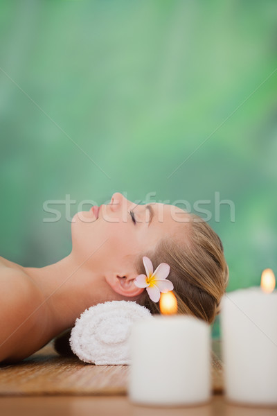 Peaceful blonde lying on bamboo mat with candles Stock photo © wavebreak_media