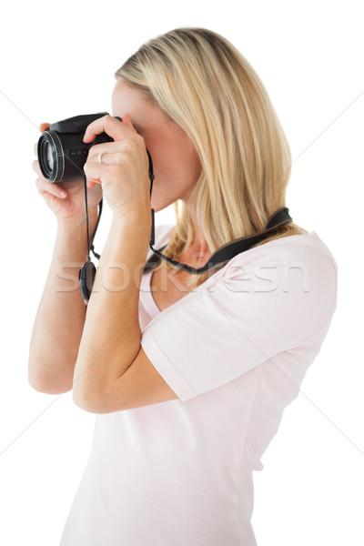 Happy blonde taking a photo on camera Stock photo © wavebreak_media
