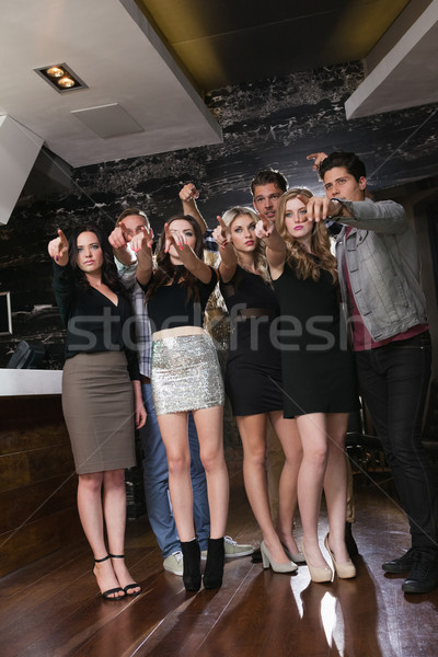 Focused friends standing and pointing away Stock photo © wavebreak_media