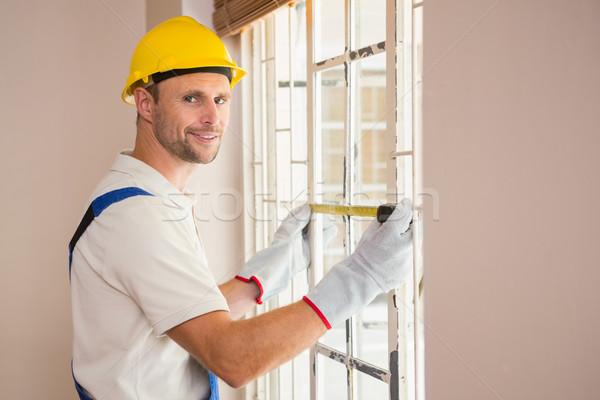 Construction worker using measuring tape Stock photo © wavebreak_media