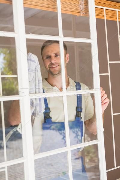 Handyman cleaning the window and smiling Stock photo © wavebreak_media