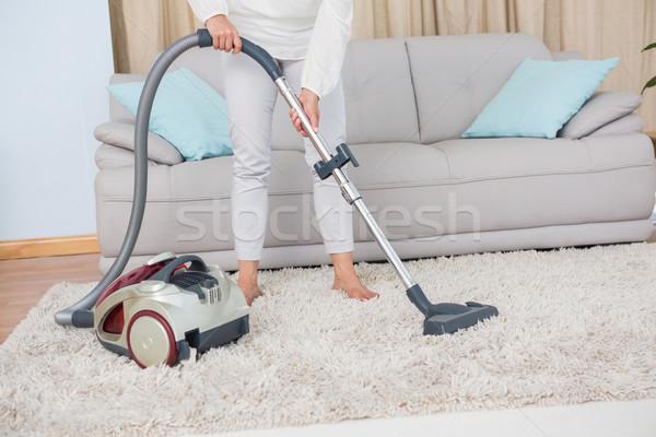 Woman using vacuum cleaner on rug Stock photo © wavebreak_media