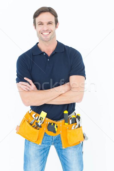 Confident man with tool belt around waist over white background Stock photo © wavebreak_media