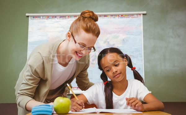 Teacher assisting little girl with homework in classroom Stock photo © wavebreak_media