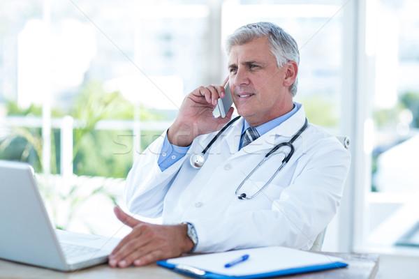 Mosolyog orvos telefonbeszélgetés asztal orvosi iroda Stock fotó © wavebreak_media