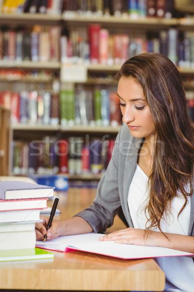 Concentrating brunette student doing her assignment Stock photo © wavebreak_media