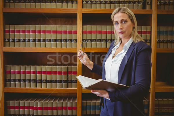 Focused librarian holding book and reading glasses Stock photo © wavebreak_media