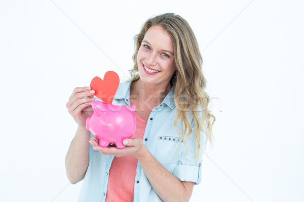 Stock photo: Smiling woman holding piggy bank and red heart