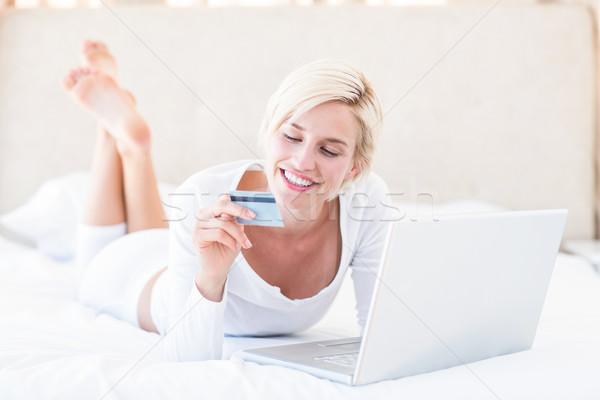 Smiling blonde woman doing online shopping Stock photo © wavebreak_media