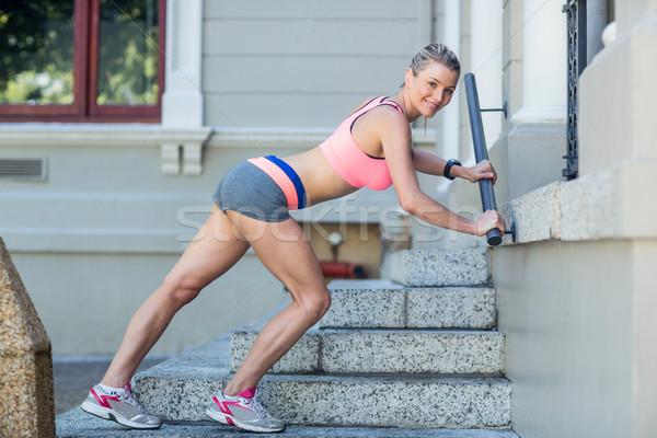 Pretty woman stretching herself on stairs Stock photo © wavebreak_media