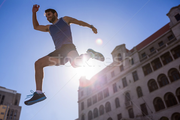 Handsome athlete leaping in front of building Stock photo © wavebreak_media
