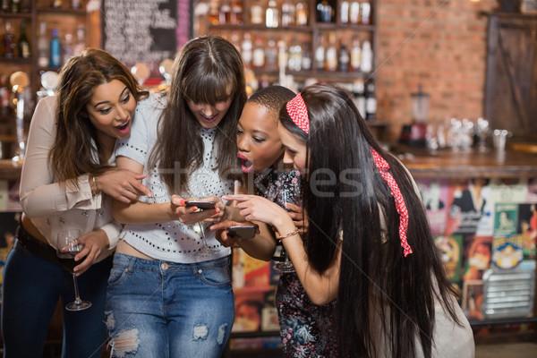 удивленный женщину глядя мобильного телефона Паб телефон Сток-фото © wavebreak_media