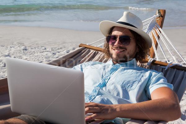 человека расслабляющая гамак используя ноутбук пляж улыбаясь Сток-фото © wavebreak_media