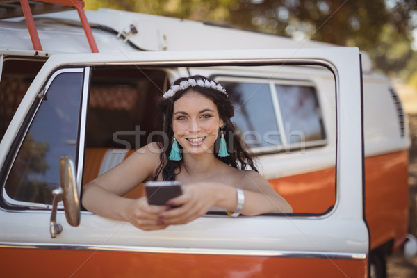 Portrait of woman using mobile phone while leaning on door Stock photo © wavebreak_media