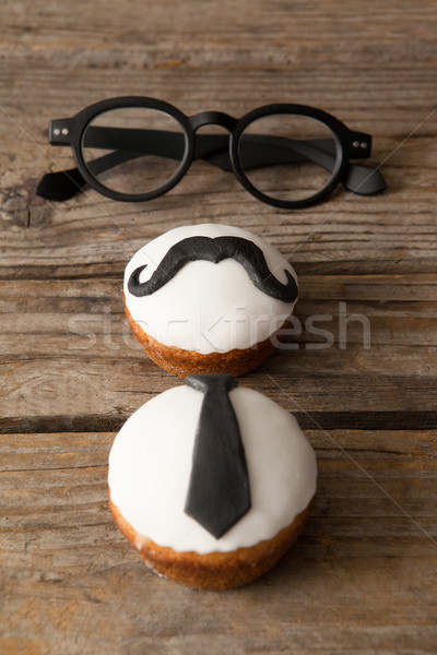 Cupcakes with mustache and necktie shape decorataion by eyeglasses on table Stock photo © wavebreak_media