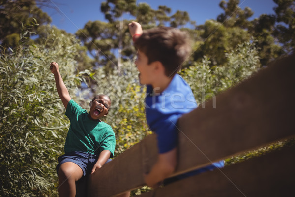 Kids cheering on wooden wall during obstacle course Stock photo © wavebreak_media