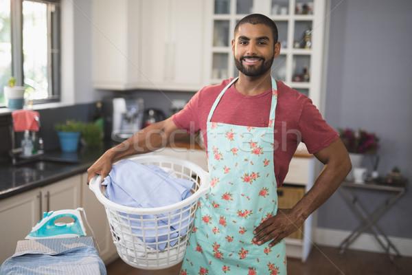 Portrait of smiling man holding laundry basket by ironing board in kitchen Stock photo © wavebreak_media