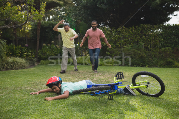 Grandfather and father running towards fallen boy with bicycle Stock photo © wavebreak_media