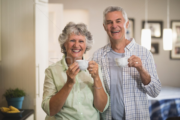 Portrait of happy senior couple holding cups in kitchen Stock photo © wavebreak_media