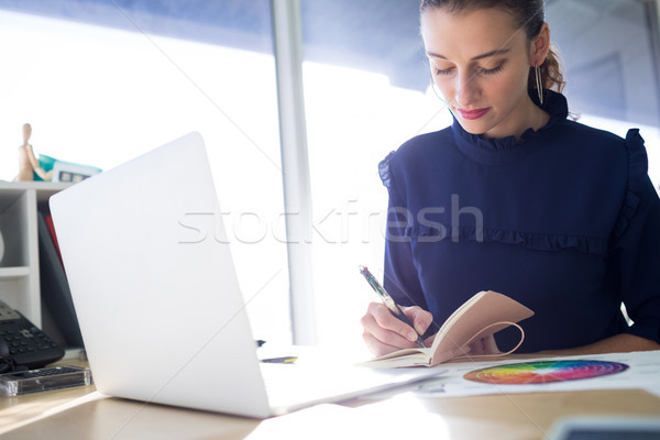 Female executive writing in diary at her desk Stock photo © wavebreak_media