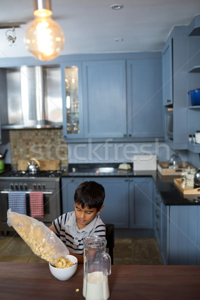 High angle view of boy pouring cereals in bowl Stock photo © wavebreak_media
